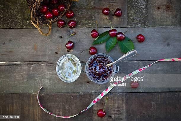 Jar of cherry jam and cherries on wood