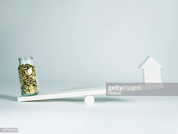 Jar of coins and a house balancing on seesaw