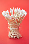 Jar of cotton swabs on red background