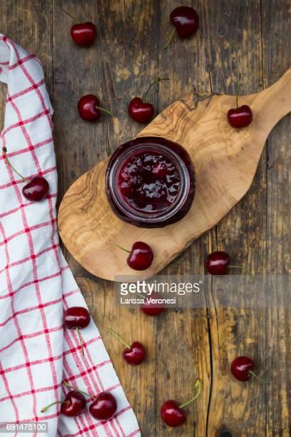 Jar of homemade cherry jam and cherries on wood