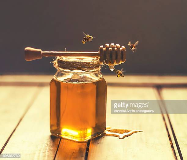 Jar of honey with honey dripper and bees