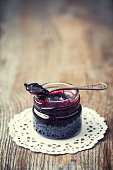 Jar of jam with spoon on old wooden table. Retro toned.