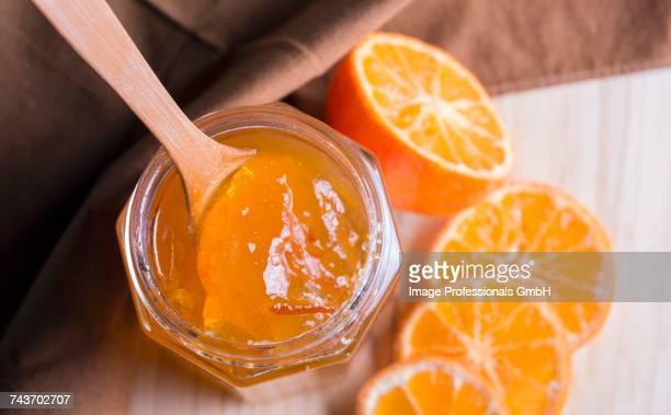 A jar of marmalade and fresh, halved oranges