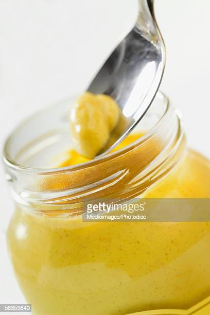 Jar of mustard and spoon with mustard above jar, extreme close-up, part of