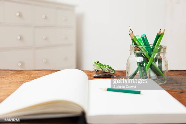 Jar of pencils and notebook on table