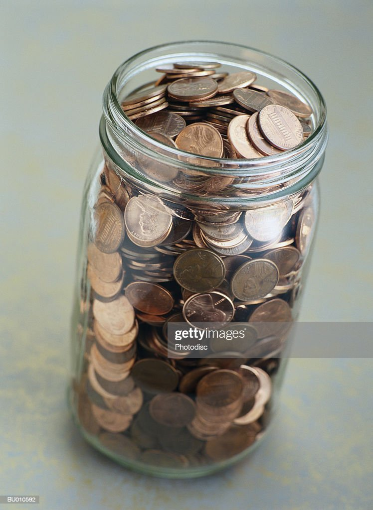 jar of pennies stock photo getty images