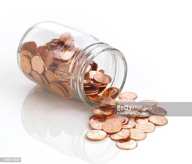 Jar of polished US pennies spilling out on white