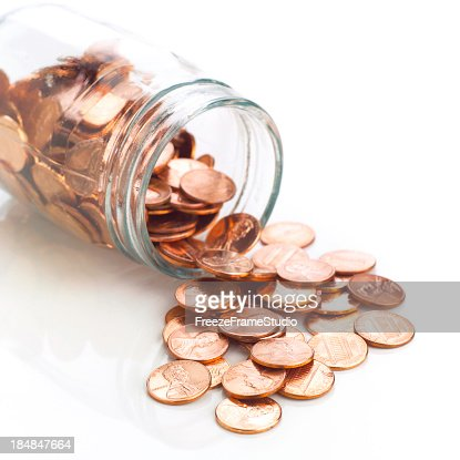 Jar of shiny US pennies spilling out on refective white
