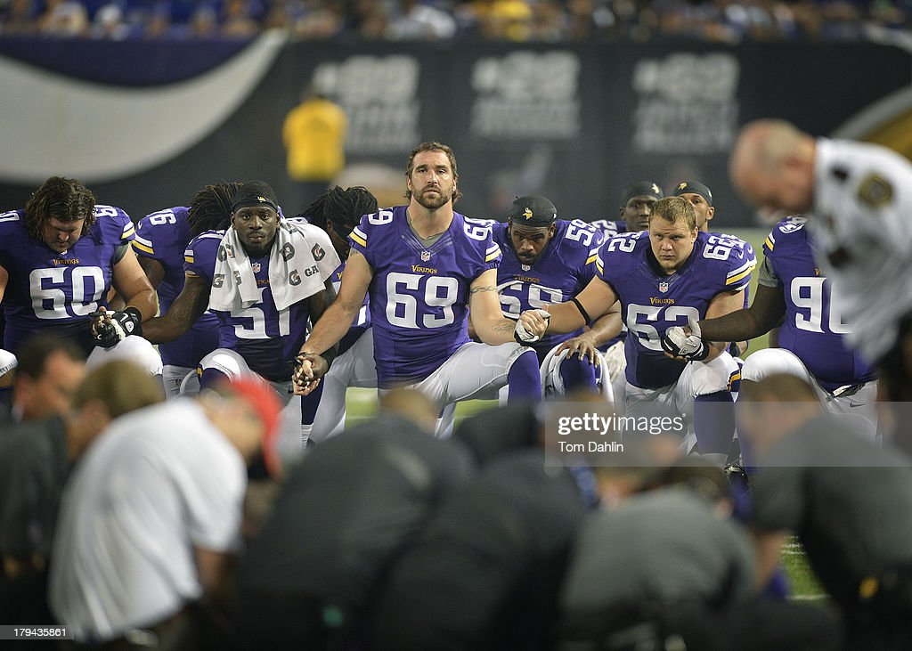 Jared Allen #69 of the Minnesota Vikings and teammates hold hands in solidarity as teammate Seth Olsen #72 is cared for by medical personnel during an NFL game against the Tennessee Titans at Mall of America Field, on August 29, 2013 in Minneapolis, Minnesota.