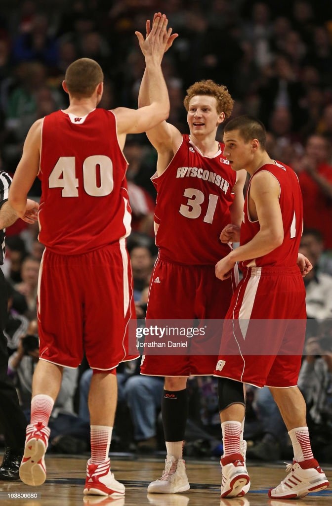 Jared Berggren #40, Mike Brueswitz #31, and Ben Brust #1 of the Wisconsin Badgers celebrate during a semifinal game of the Big Ten Basketball Tournament against the Indiana Hoosiers at the United Center on March 16, 2013 in Chicago, Illinois. Wisconsin defeats Indiana 68-56.