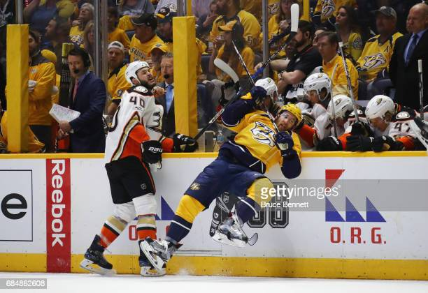 Jared Boll of the Anaheim Ducks checks Yannick Weber of the Nashville Predators during the second period in Game Four of the Western Conference Final...