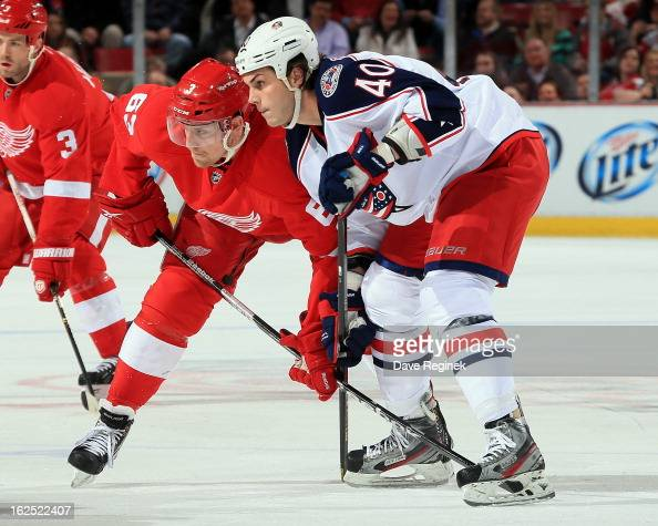 Jared Boll of the Columbus Blue Jackets battles for position on a faceoff with Joakim Andersson of the Detroit Red Wings during a NHL game at Joe...