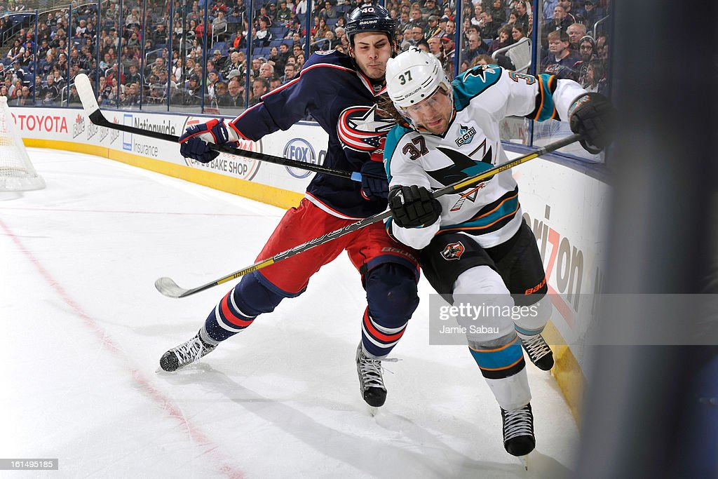 <a gi-track='captionPersonalityLinkClicked' href=/galleries/search?phrase=Jared+Boll&family=editorial&specificpeople=2238879 ng-click='$event.stopPropagation()'>Jared Boll</a> #40 of the Columbus Blue Jackets checks <a gi-track='captionPersonalityLinkClicked' href=/galleries/search?phrase=Adam+Burish&family=editorial&specificpeople=696936 ng-click='$event.stopPropagation()'>Adam Burish</a> #37 of the San Jose Sharks into the boards while chasing after a loose puck during the third period on February 11, 2013 at Nationwide Arena in Columbus, Ohio. Columbus defeated San Jose 6-2.