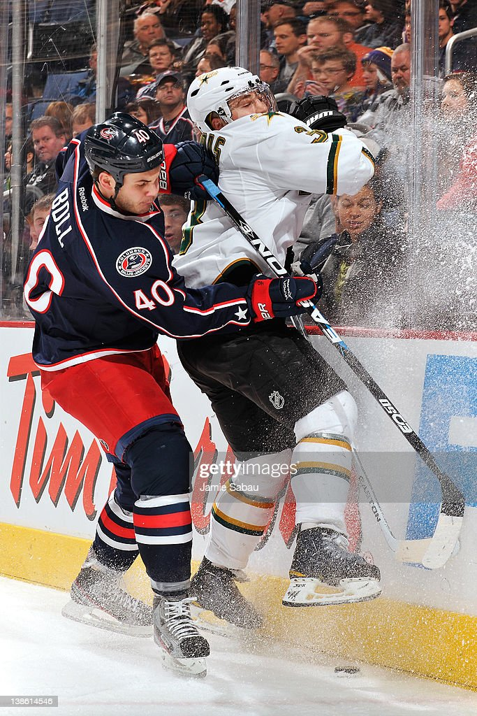 Jared Boll of the Columbus Blue Jackets checks Stephane Robidas of the Dallas Stars into the boards during the first period on February 9 2012 at...