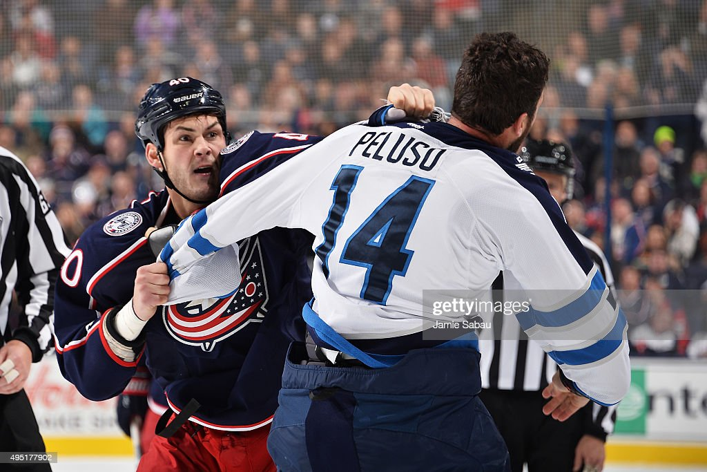Jared Boll of the Columbus Blue Jackets fights Anthony Peluso of the Winnipeg Jets during the second period on October 31 2015 at Nationwide Arena in...
