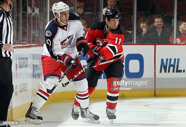 Jared Boll of the Columbus Blue Jackets skates against Dean McAmmond of the New Jersey Devils at the Prudential Center on March 23 2010 in Newark New...
