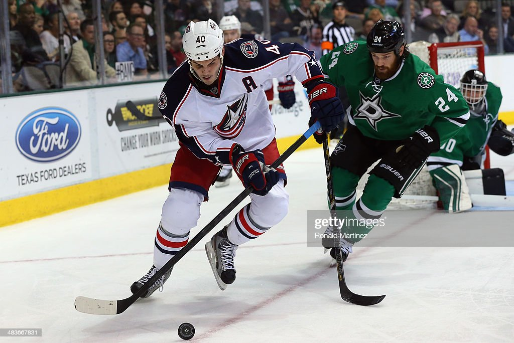 Jared Boll #40 of the Columbus Blue Jackets skates the puck past Jordie Benn #24 of the Dallas Stars in the second period at American Airlines Center on April 9, 2014 in Dallas, Texas.