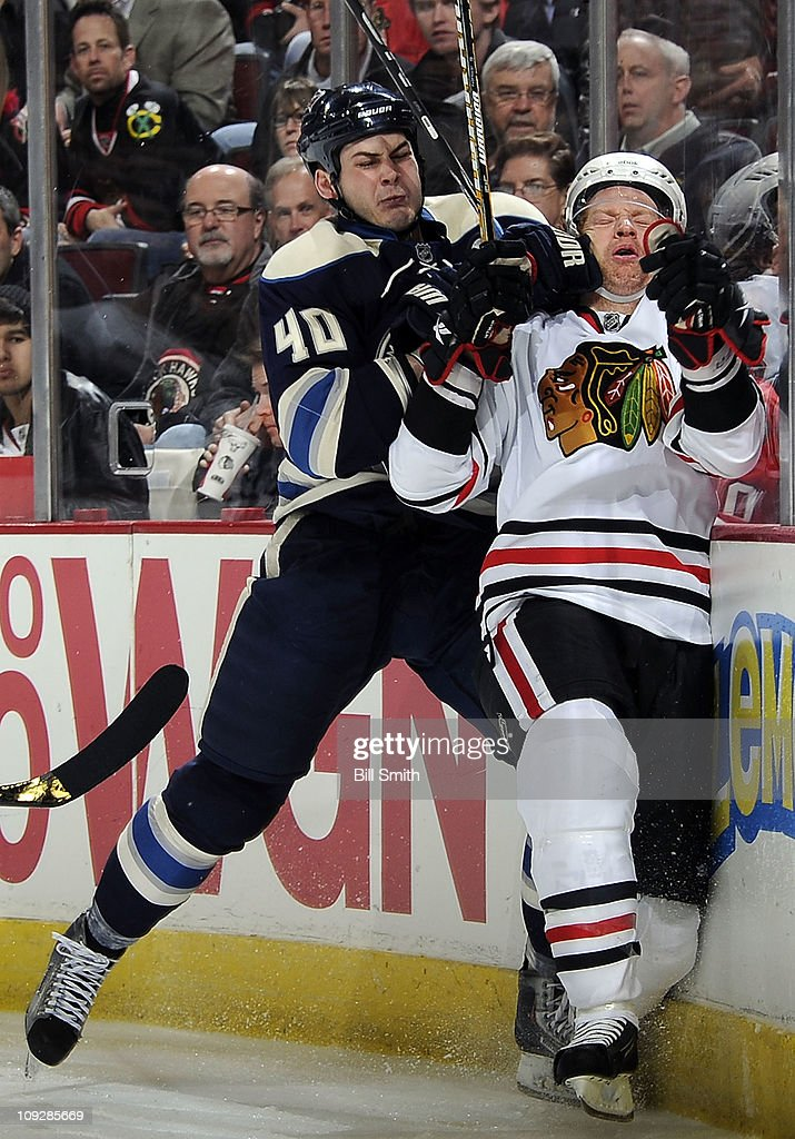 Jared Boll of the Columbus Blue Jackets slams Brian Campbell of the Chicago Blackhawks into the glass on February 18 2011 at the United Center in...