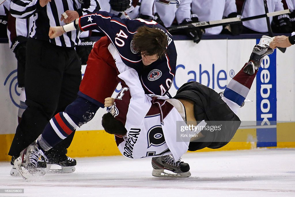 Jared Boll of the Columbus Blue Jackets throws a punch as Patrick Bordeleau of the Colorado Avalanche falls to the ice during a fight in the second...