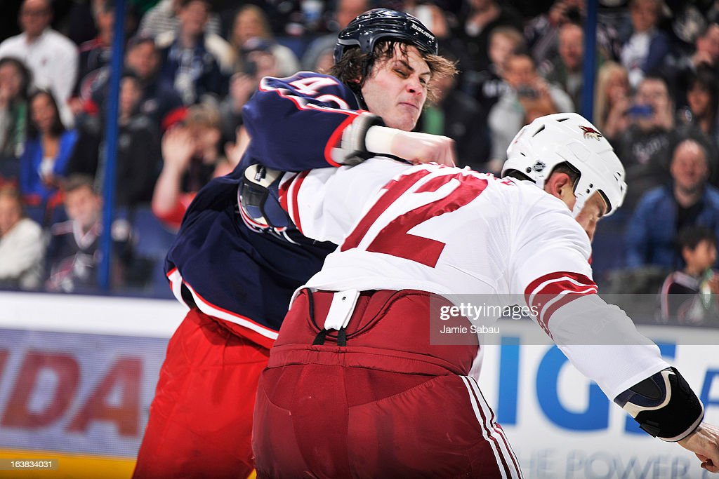 Jared Boll #40 of the Columbus Blue Jackets throws a punch at Paul Bissonnette #12 of the Phoenix Coyotes during the second period on March 16, 2013 at Nationwide Arena in Columbus, Ohio.