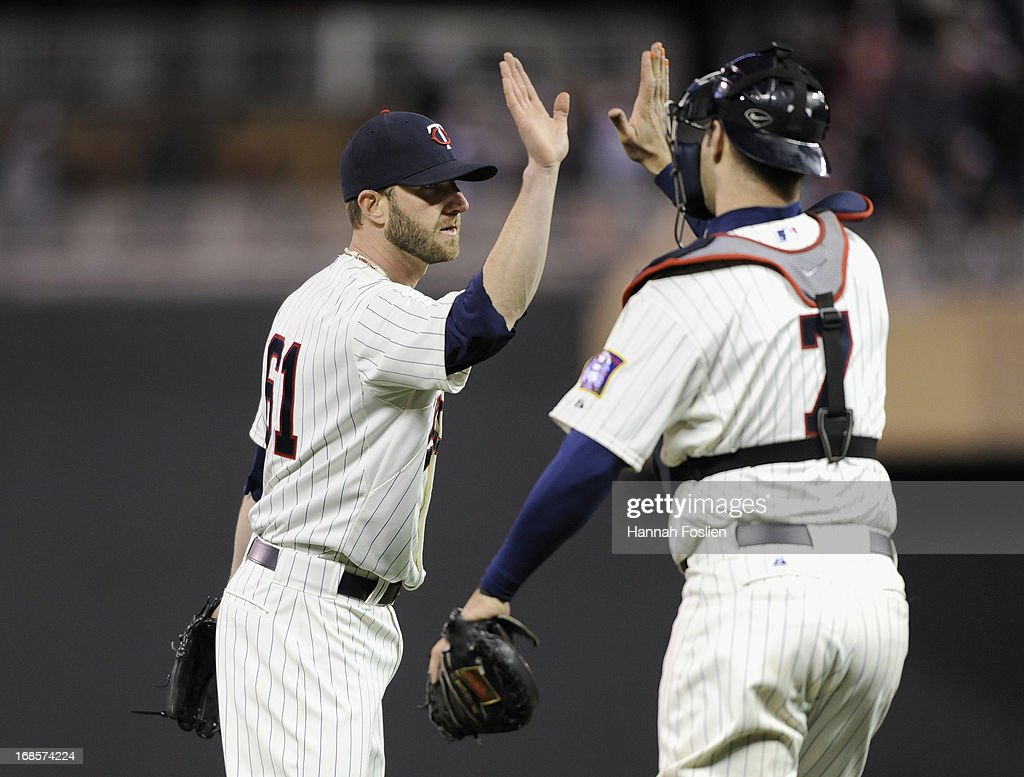 Jared Burton #61 and Joe Mauer #7 of the Minnesota Twins celebrate a win of the game against the Baltimore Orioles on May 11, 2013 at Target Field in Minneapolis, Minnesota.