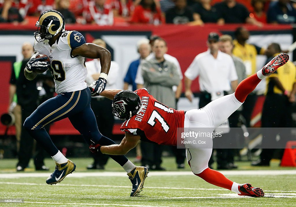 Jared Cook of the St Louis Rams tries to break a tackle by Kroy Biermann of the Atlanta Falcons at Georgia Dome on September 15 2013 in Atlanta...
