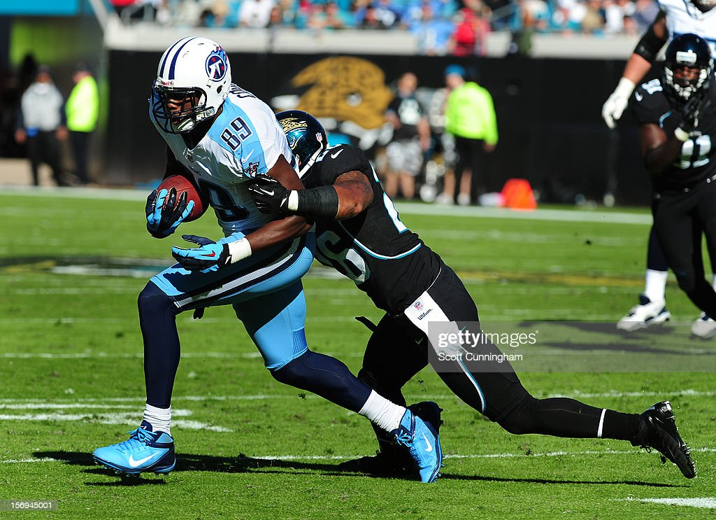 Jared Cook #89 of the Tennessee Titans runs with a catch against Dawan Landry #26 of the Jacksonville Jaguars at EverBank Field on November 25, 2012 in Jacksonville, Florida