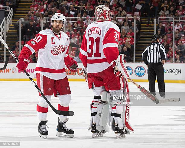Jared Coreau of the Detroit Red Wings skates to the bench in front of teammate Henrik Zetterberg after being pulled during the first period of an NHL...