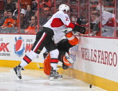 Jared Cowen of the Ottawa Senators checks Scott Hartnell of the Philadelphia Flyers to the ice on January 7 2012 at the Wells Fargo Center in...