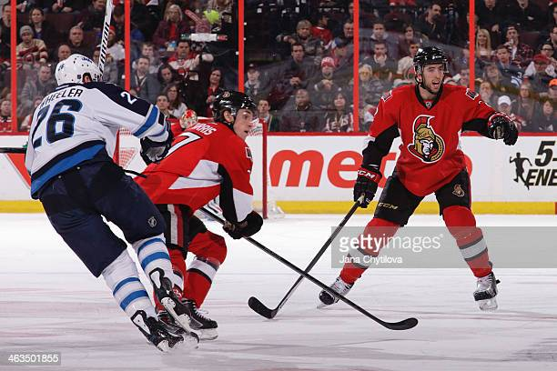 Jared Cowen of the Ottawa Senators defends against Blake Wheeler of the Winnipeg Jets as team mate Kyle Turris looks on during an NHL game at...