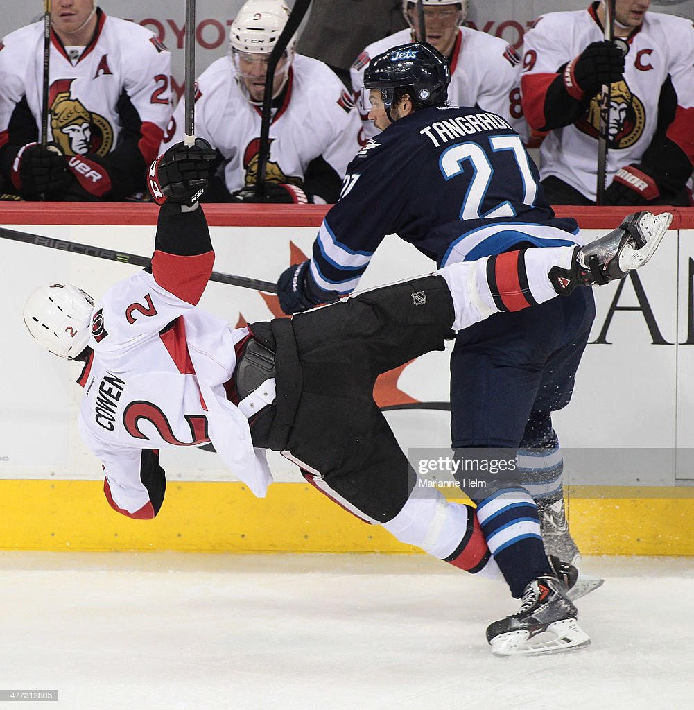 Jared Cowen #2 of the Ottawa Senators is taken down by Eric Tangradi #27 of the Winnipeg Jets in first period action in an NHL game at the MTS Centre on March 8, 2014 in Winnipeg, Manitoba, Canada.