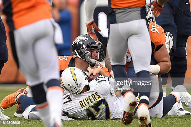 Jared Crick of the Denver Broncos and Derek Wolfe bring down Philip Rivers of the San Diego Chargers during the second quarter on Sunday October 30...