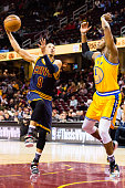 Jared Cunningham of the Cleveland Cavaliers shoots while under pressure from Jason Thompson of the Golden State Warriors during the second half at...