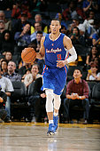 Jared Cunningham of the Los Angeles Clippers brings the ball up the court against the Golden State Warriors on October 21 2014 at Oracle Arena in...