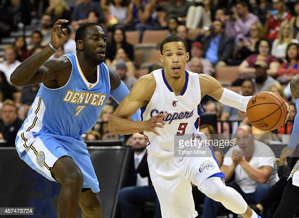 Jared Cunningham of the Los Angeles Clippers is fouled as he drives against JJ Hickson of the Denver Nuggets during their preseason game at the...