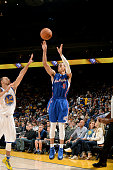 Jared Cunningham of the Los Angeles Clippers shoots a three pointer against against Stephen Curry of the Golden State Warriors on October 21 2014 at...