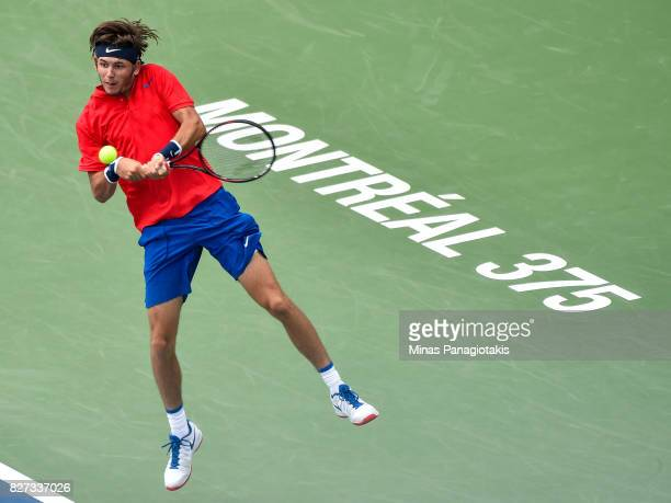 Jared Donaldson of the United States hits a backhand return shot against Lucas Pouille of France during day four of the Rogers Cup presented by...