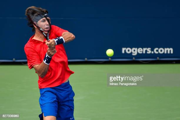 Jared Donaldson of the United States hits a return shot against Lucas Pouille of France during day four of the Rogers Cup presented by National Bank...