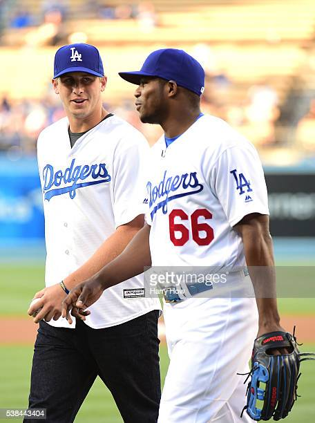 Jared Goff of the Los Angeles Rams talks with Yasiel Puig of the Los Angeles Dodgers after throwing out a ceremonial first pitch before the game...