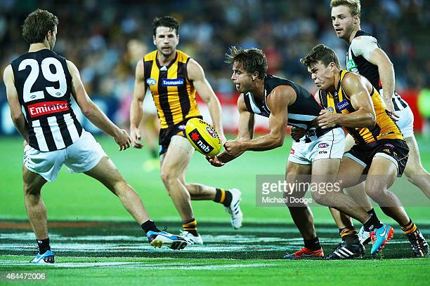 Jared Hardisty of the Hawks tackles Ben Kennedy of the Magpies who handballs to Tim Broomhead during the NAB Challenge AFL match between Hawthorn...