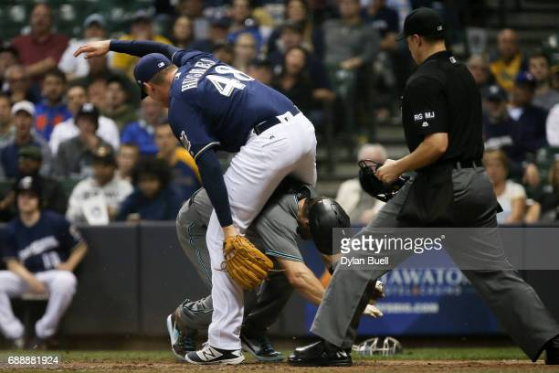 Jared Hughes of the Milwaukee Brewers leaps over Paul Goldschmidt of the Arizona Diamondbacks after Goldschmidt scored a run on a wild pitch in the...