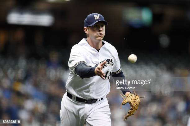 Jared Hughes of the Milwaukee Brewers makes a throw to first base during the seventh inning of a game against the San Francisco Giants at Miller Park...