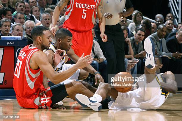 Jared Jeffries of the Houston Rockets goes for the lose ball against Ronnie Price and CJ Miles of the Utah Jazz at EnergySolutions Arena on February...