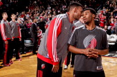 Jared Jeffries of the Portland Trail Blazers speaks with teammate Ronnie Price before playing against the Milwaukee Bucks on January 19 2013 at the...
