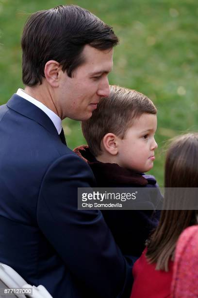 Jared Kushner senior advisor and soninlaw to US President Donald Trump holds his son Joseph Kushner before the pardoning ceremony for the National...
