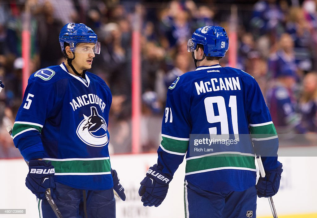 Jared McCann and Luca Sbisa of the Vancouver Canucks talk during a break in NHL action against the Calgary Flames on October 10 2015 at Rogers Arena...