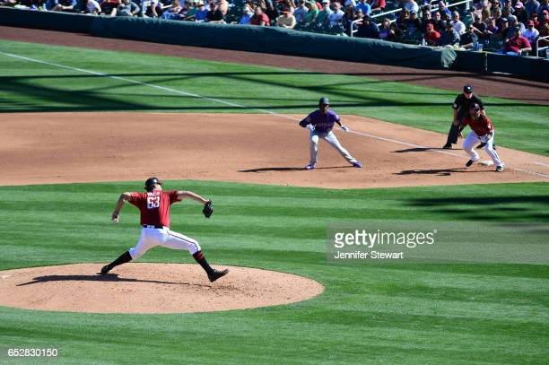 Jared Miller of the Arizona Diamondbacks delivers a pitch Raimel Tapia of the Colorado Rockies leads off first base during the spring training game...