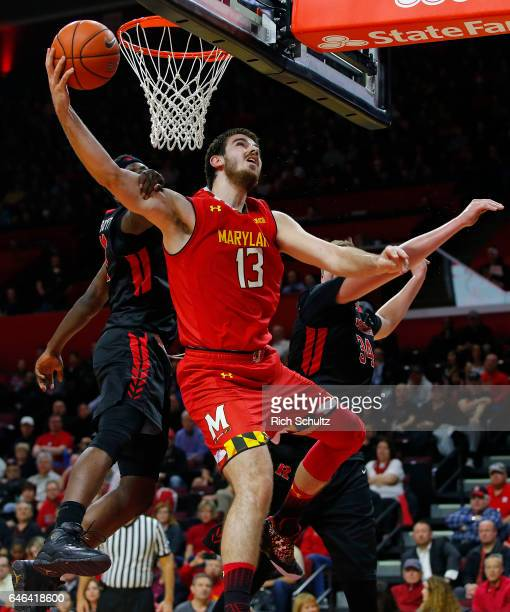 Jared Nickens of the Maryland Terrapins attempts a shot between Eugene Omoruyi and CJ Gettys and Corey Sanders of the Rutgers Scarlet Knights during...