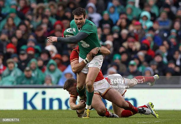 Jared Payne of Ireland is tackled by Rhys Priestland and Jamie Roberts of Wales during the RBS Six Nations match between Ireland and Wales at the...