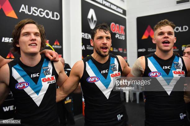 Jared Polec Travis Boak and Dan Houston of the Power sing the club song after defeating the Suns during the round 23 AFL match between the Port...